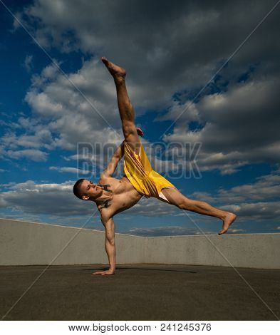 Tricking On Street. Martial Arts. Man Kick With Hand Support Barefoot. Taken From Low Angle Against