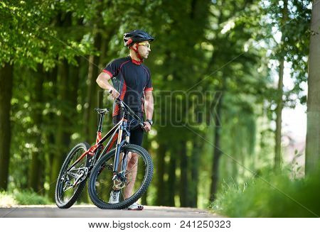 Man Professional Cyclist In Cycling Clothing And Helmet Looking Away In Distance, Taking Break From
