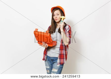 Young fun woman in protective hardhat holding opened case with instruments or toolbox and beating herself on face with toy hammer isolated on white background. Renovation room. Repair home concept poster