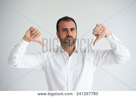 Portrait Of Confident Mid Adult Businessman Showing Thumb Down. Bearded Caucasian Man Wearing White