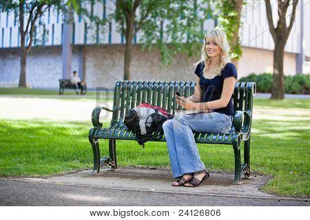 Joven estudiante sosteniendo el teléfono celular mientras estaba sentado en el campus de la Universidad