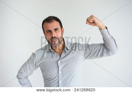 Portrait Of Serious Mid Adult Businessman Showing Muscle. Caucasian Bearded Man Wearing Striped Blue
