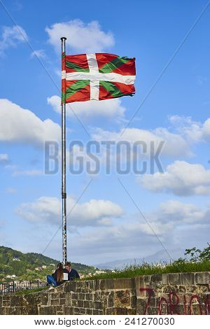 San Sebastian, Spain - May 11, 2018. Two Young People Sitting Under The Mast Of A Ikurrina, Basque C