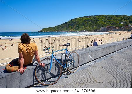 San Sebastian, Spain - May 11, 2018. A Young Men With Their Bike Parked In Front Of  Zurriola Beach