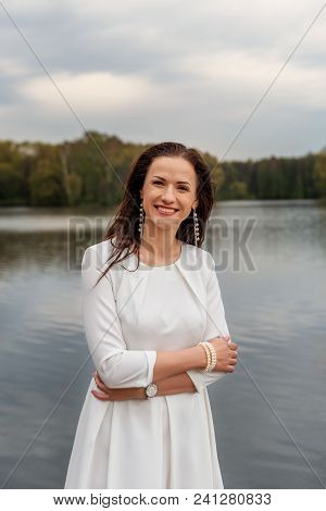 Smiling Optimistical Confident Woman Coach Standing On Waterfront City River Lake In White Dress