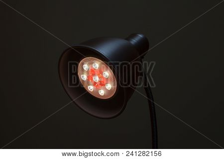 Close-up Of A Led Lamp White And Red Color. Round Table Lamp With A New Technology Lamp On Black Bac