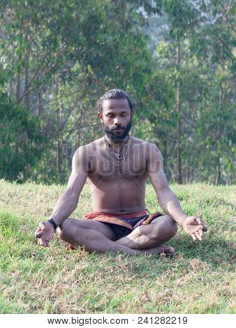 Athletic Indian Man Meditating In Lotus Yoga Pose In Forest In Kerala, South India