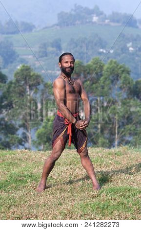 Athletic Indian Man Doing Breathing Exercises In Standing Pose On Green Grass In Kerala, South India