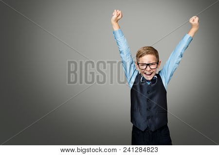Child In Glasses Raising Up Arms, Happy Smiling Kid Boy In Eyeglasses And Suit Raised Hands Over Gra