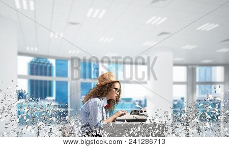 Young Woman Writer In Hat And Eyeglasses Using Typing Machine While Sitting At The Table Indoors Amo