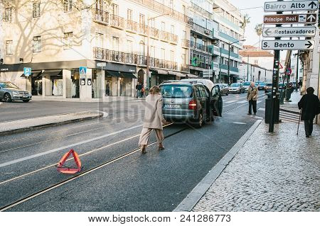 Lisbon, Portugal 01 May 2018: Emergency Or Driver Or Girl Puts Road Sign. Car Costs On Emergency Sig