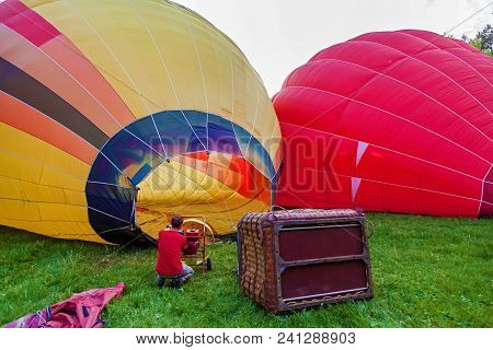 A Balloon With A Basket Lies On The Ground, Equipment For Filling The Balloon With Cold And Hot Air.