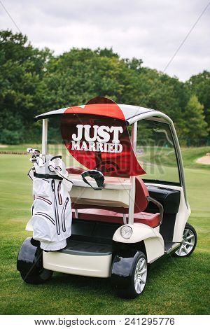 Just Married Sign On Red Heart On Empty Golf Car Outdoors. Wedding Concept. Golf Cart On Golf Course