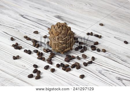 Pine Nuts And Pine Cone On A White Wooden Background