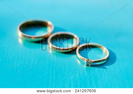 Three Wedding Rings On Turquoise Wooden Background, Selective Focus. Engagement Ring With Diamond, B