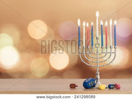 Hanukkah Jewish holiday background with menorah (Judaism candelabra)  burning candles and traditional Dreidrel game toy on wood table and on autumn bokeh sun flare poster