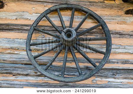 Old Weathered Wagon Wheel On Log Cabin Wall