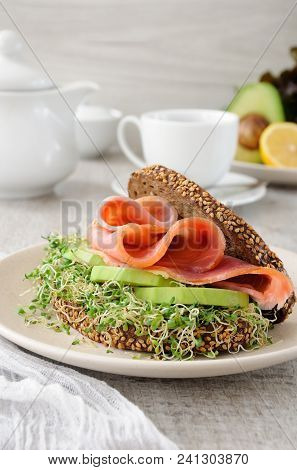 Sandwich Of Rye Bread With Cereals, Slices Of Ham And Avocado With Sprouts Of Sprouted Alfalfa.