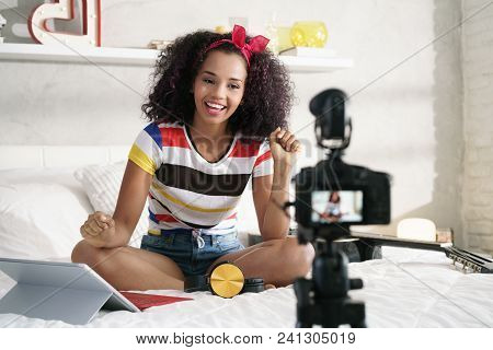 Happy Girl At Home Speaking In Front Of Camera For Vlog. Young Black Woman Working As Blogger, Recor