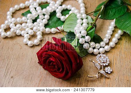 Pictured In The Photo Beautiful Red Rose With Pearl Beads On A Beige Background.