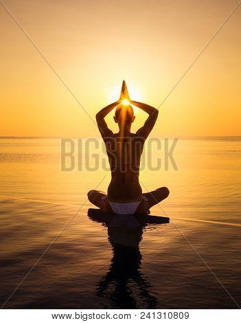 Woman has meditation and Yoga at infinity pool during sunset. Maldives