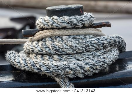 Mooring Rope With A Knotted End Tied Around A Cleat On A Wooden Pier
