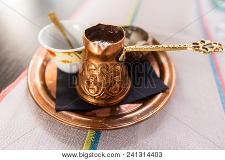 Turkish or bosnian coffee served  in a traditional copper pot