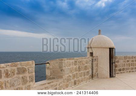 Old city wall in Dubrovnik, Croatia overlooking blue mediterranean sea with cloudy skies