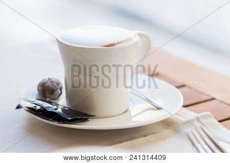 Coffee with thick foam cappuccino or macchiato on a white porcelain mug and saucer