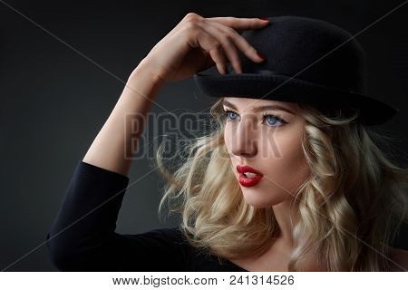 Low Key Portrait Of Goargeous Glamour Woman With Blond Hair, Wearing A Hat, Studio Shot, Blurred Bac