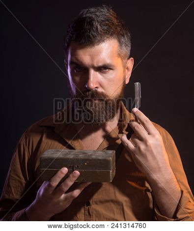 Brutal Caucasian Hipster, Serious Bearded Man With Long Beard Holds In Hands Dangerous Razor, Wooden