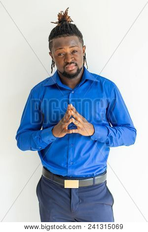 Pensive Frowning Black Businessman Touching Tips Of Fingers And Looking At Camera. Contemplative You