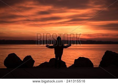 Young Child Standing Silhouetted On Rocks Overlooking A Vivid Orange Marine Sunset With Reflections