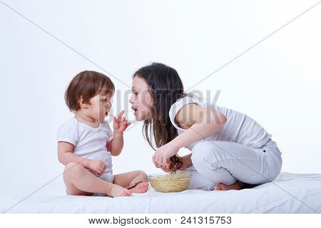 Cute Little Playful Sisters Eating Yummy Pasta In White Studio Background