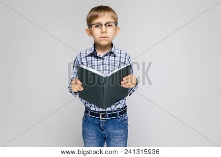 Portrait Of A Boy On A Gray Background. A Boy With Glasses. The Boy Is Reading A Book