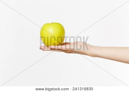 Close Up Female Holds In Hand Green Fresh Apple Isolated On White Background. Proper Nutrition, Vege