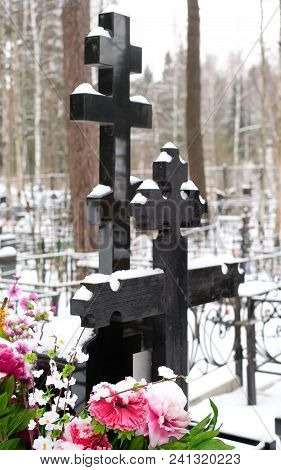 Black Crosses And Artificial Flowers On The Grave Of An Orthodox Cemetery In The Winter