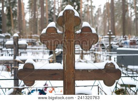 Beautiful Wooden Cross Of Traditional Shape And Artificial Flowers On The Grave Of The Orthodox Ceme