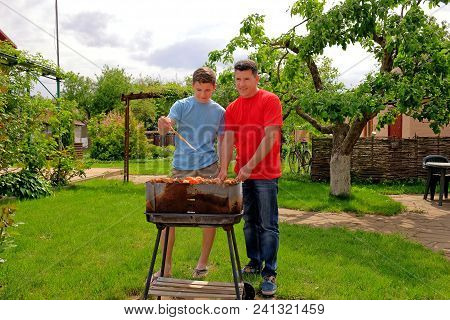 Attractive White Father And Son Are Smiling And Grilling Kebabs On Open Air Near Their Home