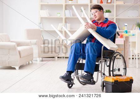 Disabled man repairing chair in workshop