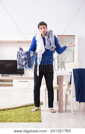 Young man collecting dirty clothing for laundry