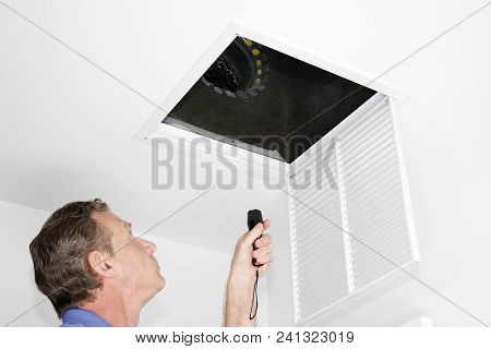 Male Looking Up Into A Ceiling Air Intake Duct With A Flashlight Checking For Maintenance. Person Wi
