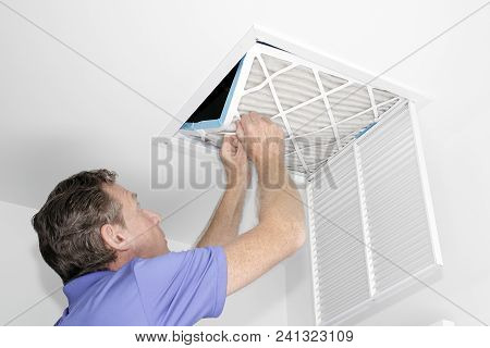 Mature Man Taking Out A Dirty Air Filter From A Home Ceiling Air Return Vent. Male Removing A Dirty