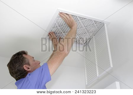 Male Pushing A Clean Air Filter Into Place In The Ceiling With Both Hands. One Fresh Furnace Air Fil