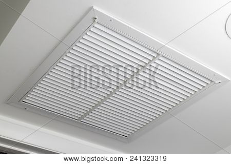 One Large White Painted Metal Furnace Air Vent Grill With Many Openings On A Ceiling Close-up. Squar