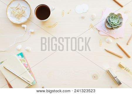 Female Home Office Desk Table In Pastel Tones. Workspace With Notebooks, Cup Of Coffe And Decoration