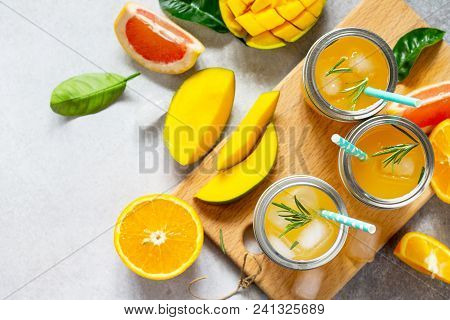 Fresh Refreshing Summer Drinks. Multifruit Drinks Of Citrus And Mango With Ice, Smoothies On A Light