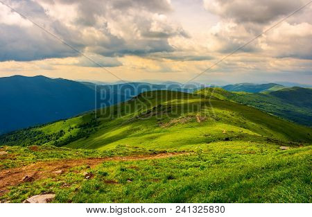 Beautiful Mountain Landscape With Grassy Hills. Sky With Fluffy Clouds. Foot Path In To The Distance