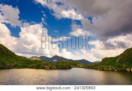 Gorgeous Cloudscape Over The Capra Lake. Amazing Fagaras Mountain Ridge In The Distance.