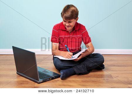 Foto eines Studenten, der seine Hausaufgaben saß auf dem Boden seinen Laptop zu betrachten, während in einem nicht zu schreiben